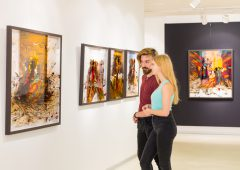 In a exhibition centre, young couple  visits an art exhibition and watches artist's collection on the wall.
